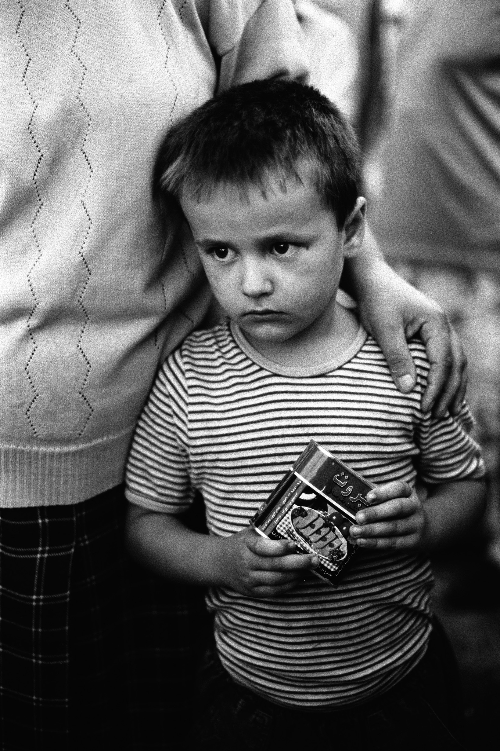 Asmir Kadijic, 7, holds his and his mother's ration of canned spam like meat. Asmir found the bodies of his father, uncle and grandfather, lying in front of his house, shortly after they were executed by Serbian soldiers.